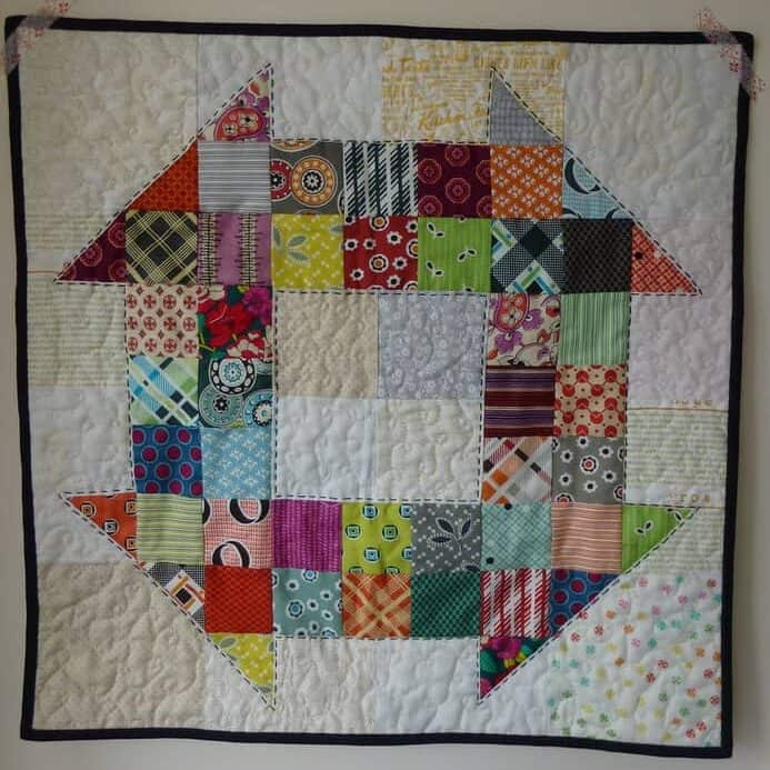 Scrappy Churn Dash mini quilt made with Denyse Schmidt fabrics and low volume background by fabricandflowers.